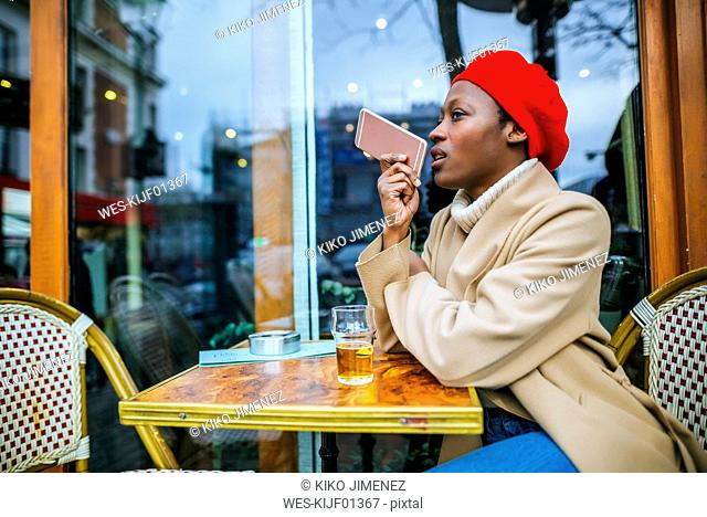Young woman in Paris sitting in cafe and leaving a voice message