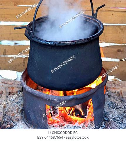 black pot with the fire lit and the dense white smoke
