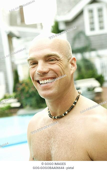 Young man smiling by pool