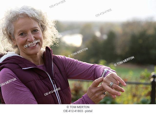 Portrait smiling, confident active senior woman exercising, checking smart watch