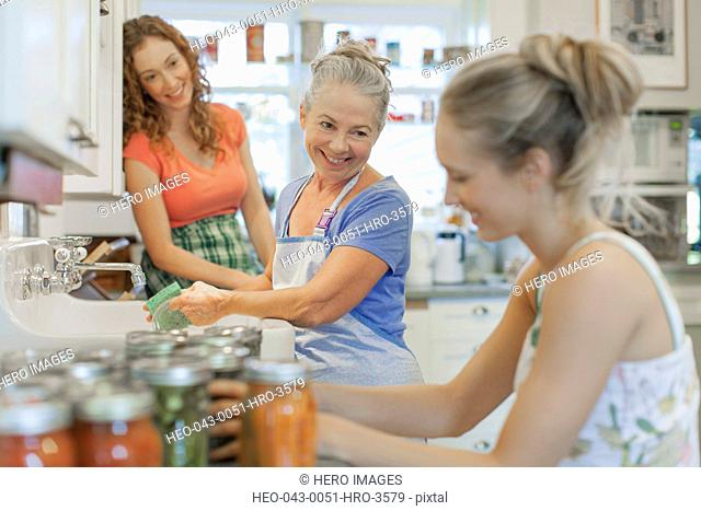 Mother and daughters working in kitchen together