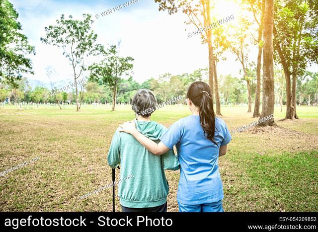 nurse helping senior woman to walk around the park