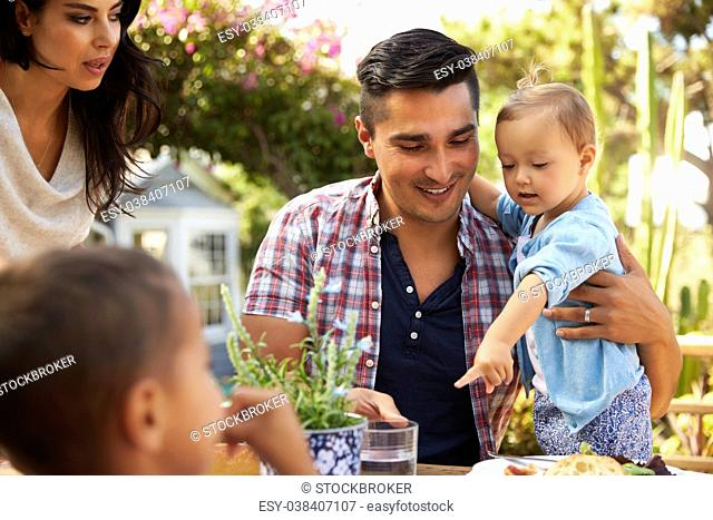 Family At Home Eating Outdoor Meal In Garden Together