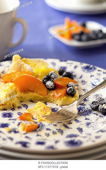 Sweet omelette with blueberries, peaches and icing sugar, partially eaten