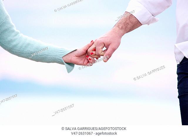Wedding couple holding hands on the beach of Saler, Valencia, Spain, Europe