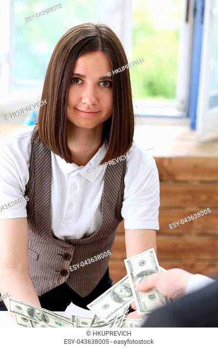 Businessman and business woman counting cash on the table at the office with hands very many dollars salary for the near future