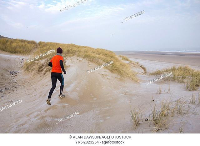 The Headland, Hartlepool, north east England. United Kingdom. A mature jogger runs over frost covered dunes on a bitterly cold January morning on the north east...