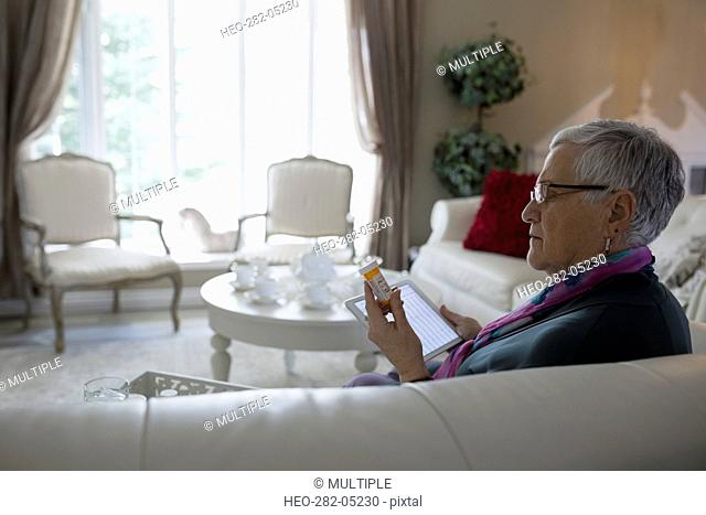 Senior woman with digital tablet checking prescription label