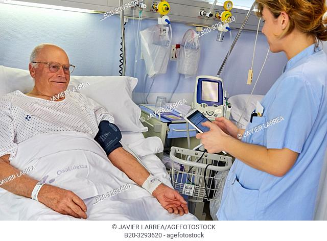 Nurse taking a patient's blood pressure, Tablet, Hospital room, Hospital Donostia, San Sebastian, Gipuzkoa, Basque Country, Spain