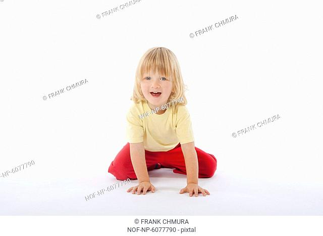 Boy with long blond hair sitting on the floor