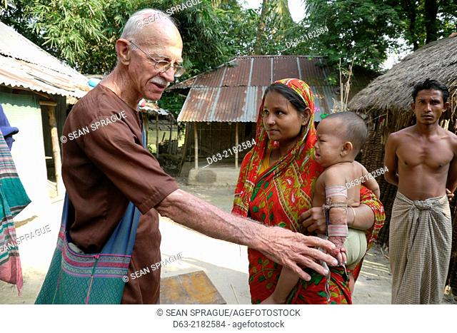 BANGLADESH. American Catholic missionary priest in Narail. Visiting a sick child who he will refer for medical treatment