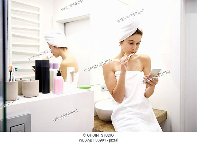 Young woman in bathroom brushing her teeth while reading messages on mobile phone