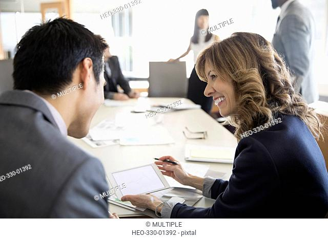 Smiling businesswoman and businessman using digital tablet in conference room meeting