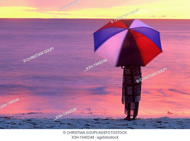 woman with an umbrella on a beach of Denis island, Republic of Seychelles, Indian Ocean