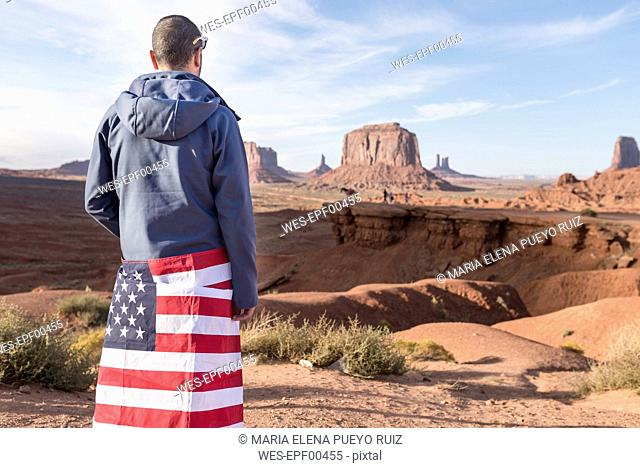 USA, Utah, back view of young man with American flag at Monument Valley