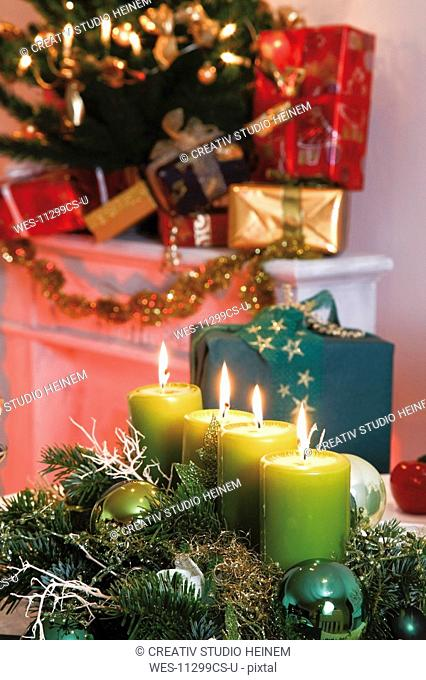 Christmas decoration with burning candles, in background christmas presents