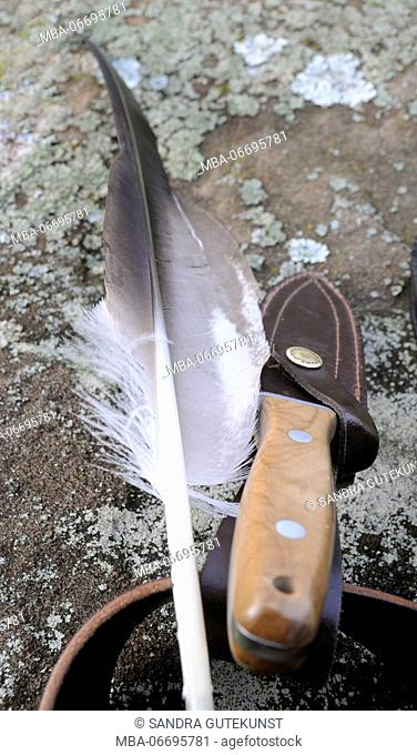 Eagle feather and falconer's knife on stone with patina, close-up