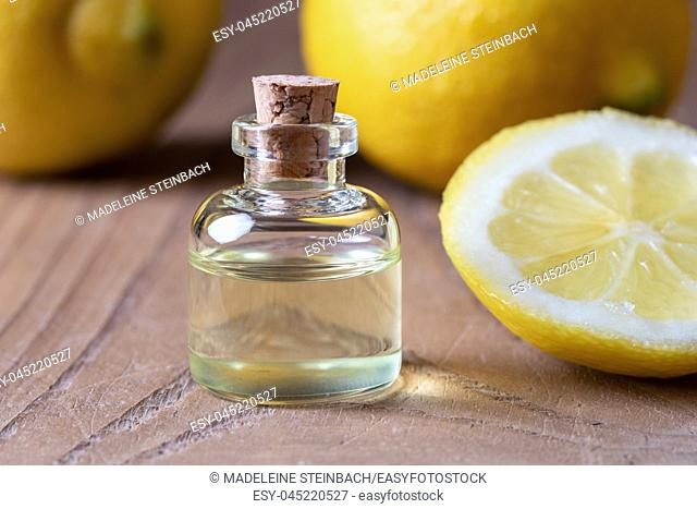 A bottle of citrus essential oil with fresh lemons