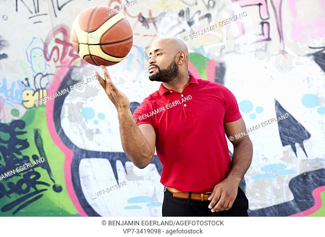 Athletic man spinning basketball on fingers in front of a wall with a graffiti painted on it. Frankfurt, Germany