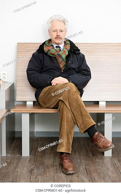 elderly man, sitting patiently in the waiting room of a medical practice, waiting for his turn