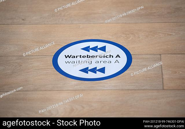 """18 December 2020, Hamburg: A sticker with the bilingual inscription """"""""Wartebereich A - waiting aerea A"""""""" is stuck on the floor in the vaccination centre"""