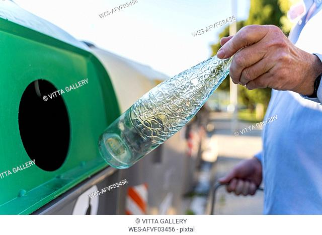 Close-up of man putting bottle into bottle bank