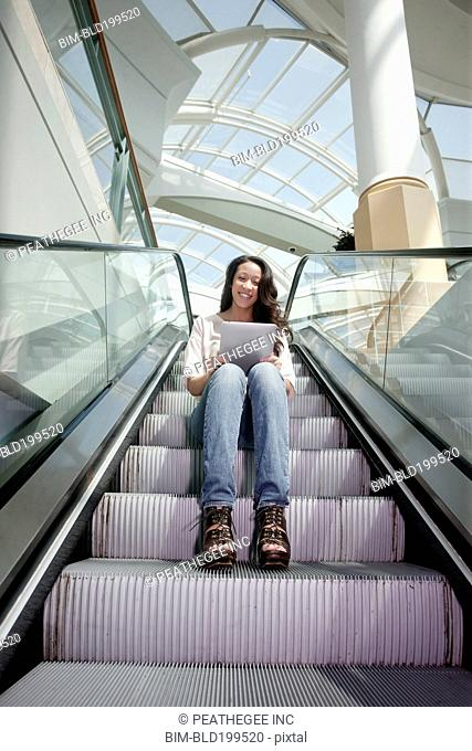 Woman on escalator using digital tablet