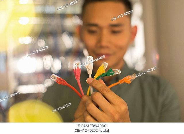 Male IT technician examining multicolor connection plugs