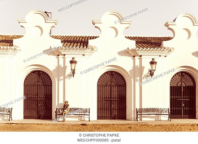 Spain, Andalusia, El Rocio, female tourist sitting in front of Ermita del Rocio