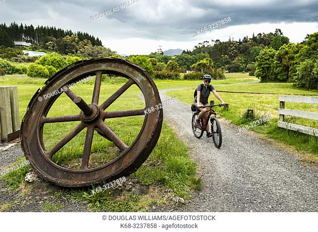 Woman cycles by the Victoria Battery Tramway and Museum on the Hauraki Rail Trail, bicycling path on the north island in New Zealand