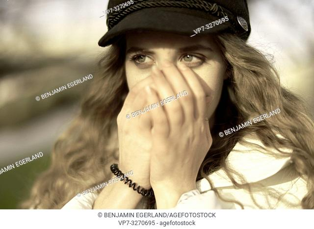 young woman, hands covering mouth, in city Cottbus, Brandenburg, Germany
