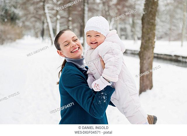 Portrait of happy baby girl having fun with her mother in snow-covered landscape