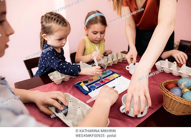 Mother and children painting Easter eggs on table at home