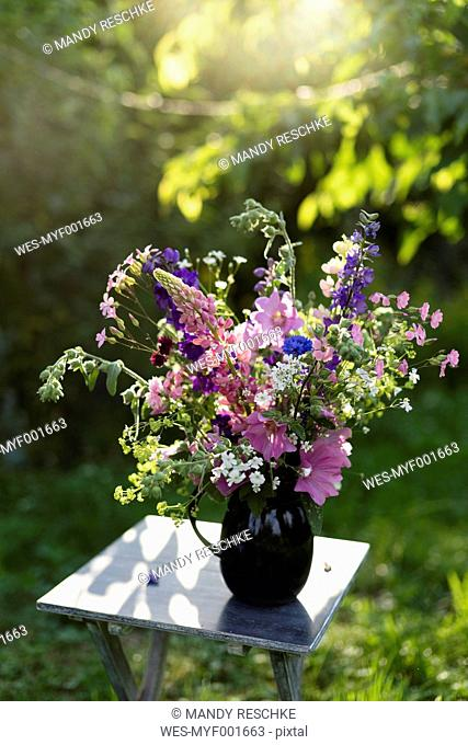 Summer flowers in vase, lupine, hollyhock, cornflower, lady's mantle and bellflower