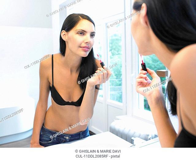 Woman applying makeup, in bathroom