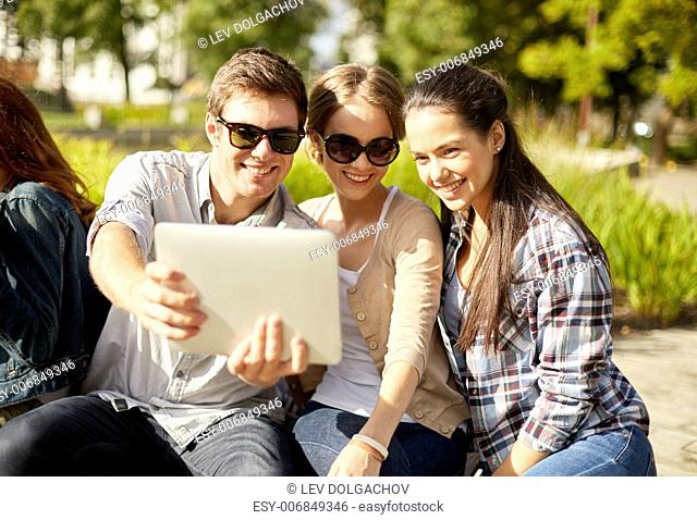 summer, education, technology and people concept - group of students or teenagers with laptop computers sitting on bench outdoors