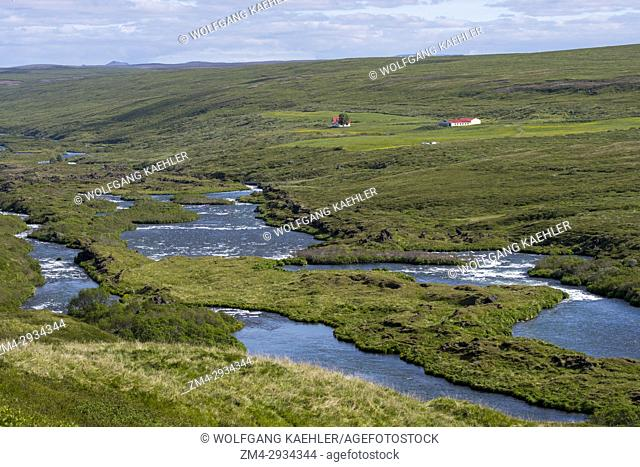 Landscape with a river flowing between green hills and a farm near Lake Myvatn in Northeast Iceland