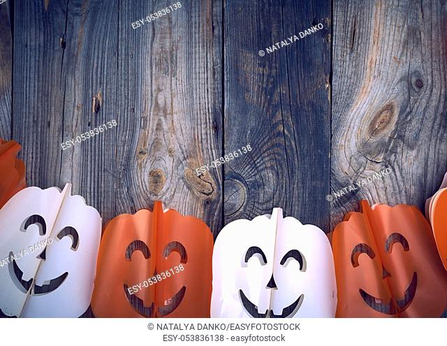 plastic garland on with carved figures of pumpkins, gray wooden background, backdrop for Halloween