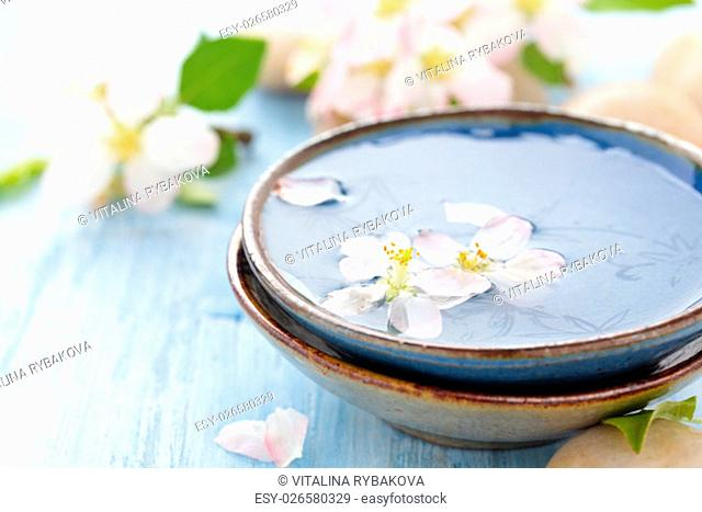 Scented oil and spring flowers for spa and aromatherapy on wooden table