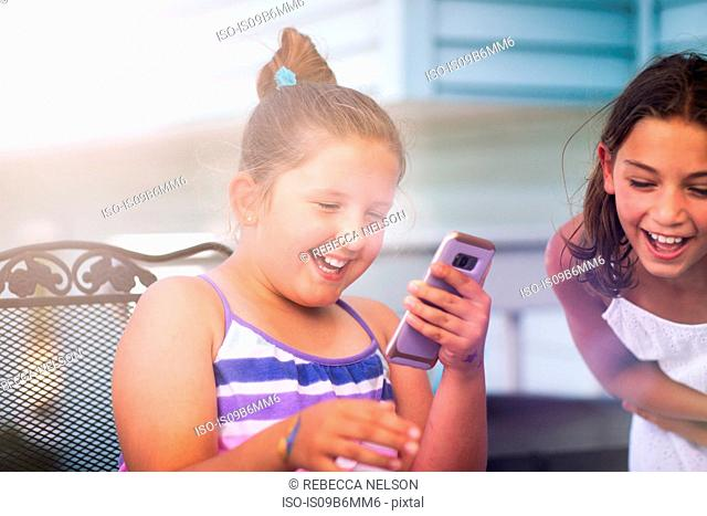 Siblings enjoying game on smartphone