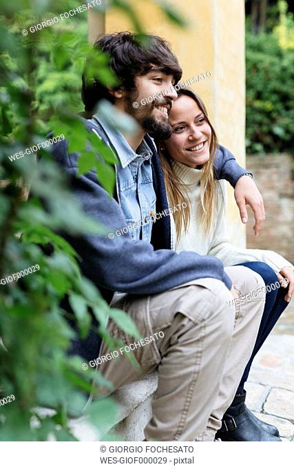 Happy young couple sitting arm in arm having a rest