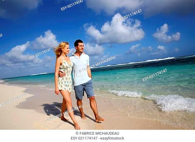 Young couple walking on a sandy beach