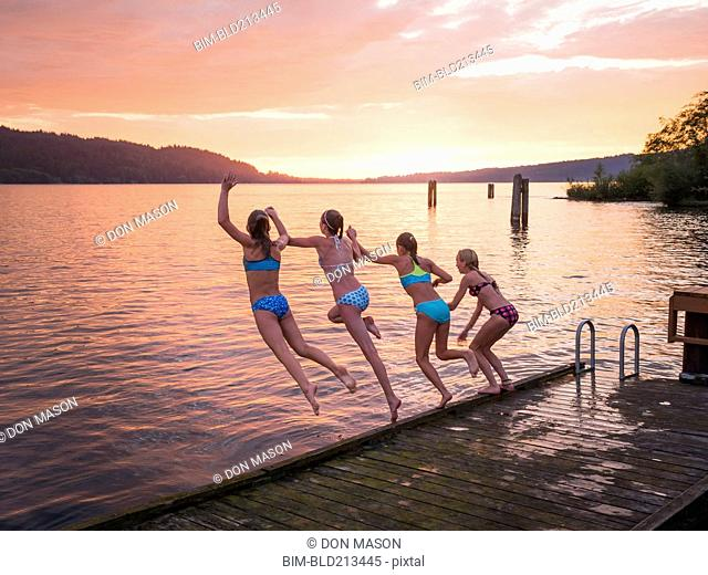 Girls jumping into lake from wooden dock