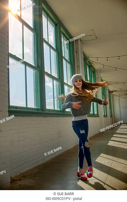 Teenage girl with long brown hair spinning in dance studio, portrait