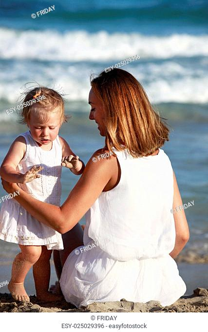 Happy mother holding her daughter on the beach. Mallorca