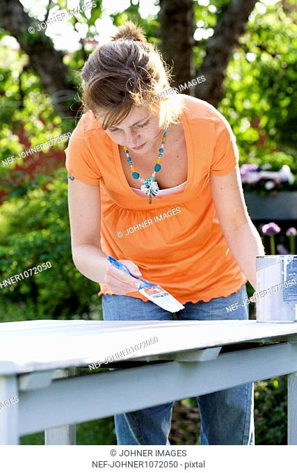 Young woman painting outdoor table