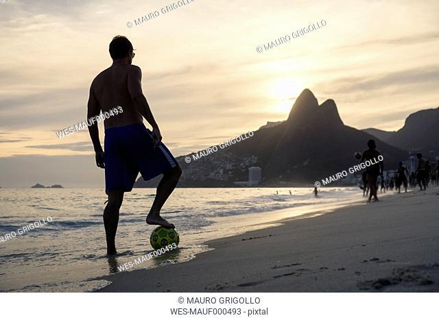 Brazil, Rio De Janeiro, man standing with ball on Ipanema beach