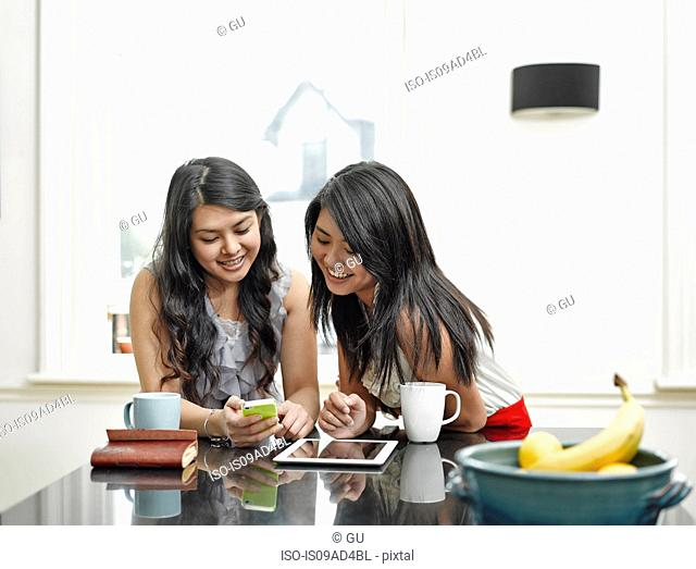 Two young women looking at mobile phone at kitchen counter