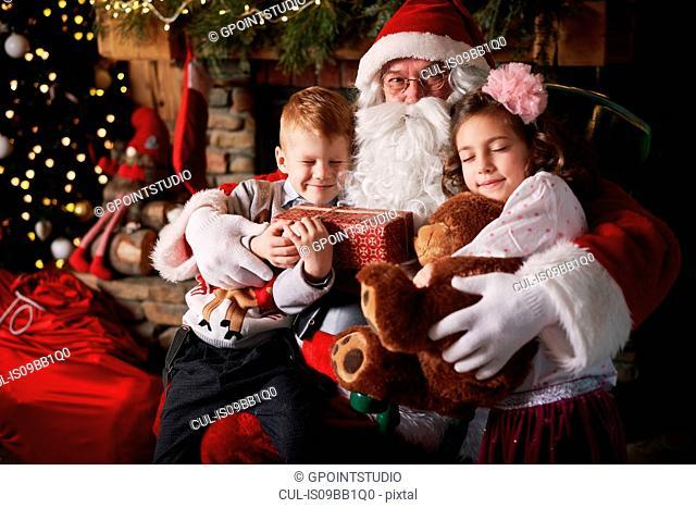 Young girl and boy visiting Santa, holding gifts