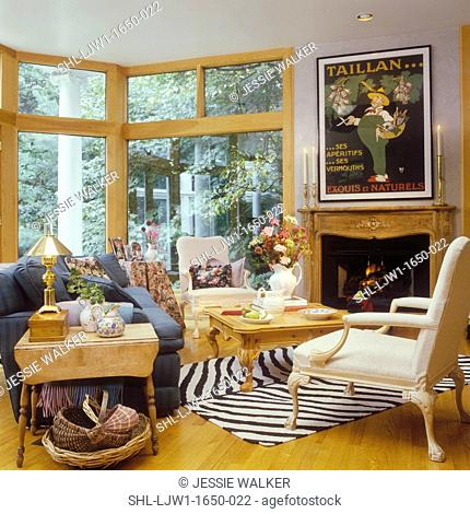 LIVING ROOMS - Sitting area with fireplace, antique mantle, large windows, zebra print rug, white arm chairs, oak coffee table, wood floor, French poster